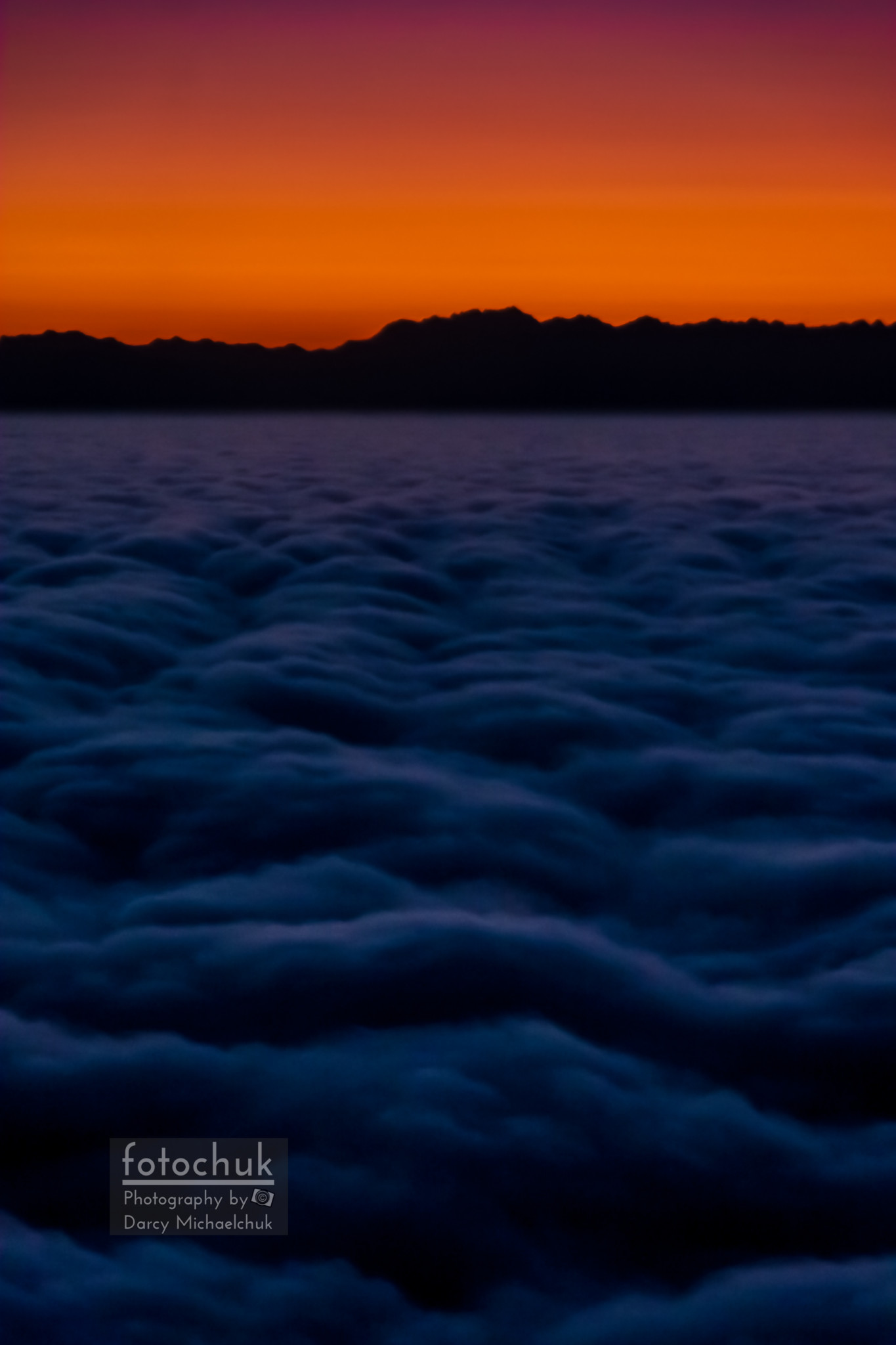 Mountain Silhouette Over Sea of Clouds Portrait