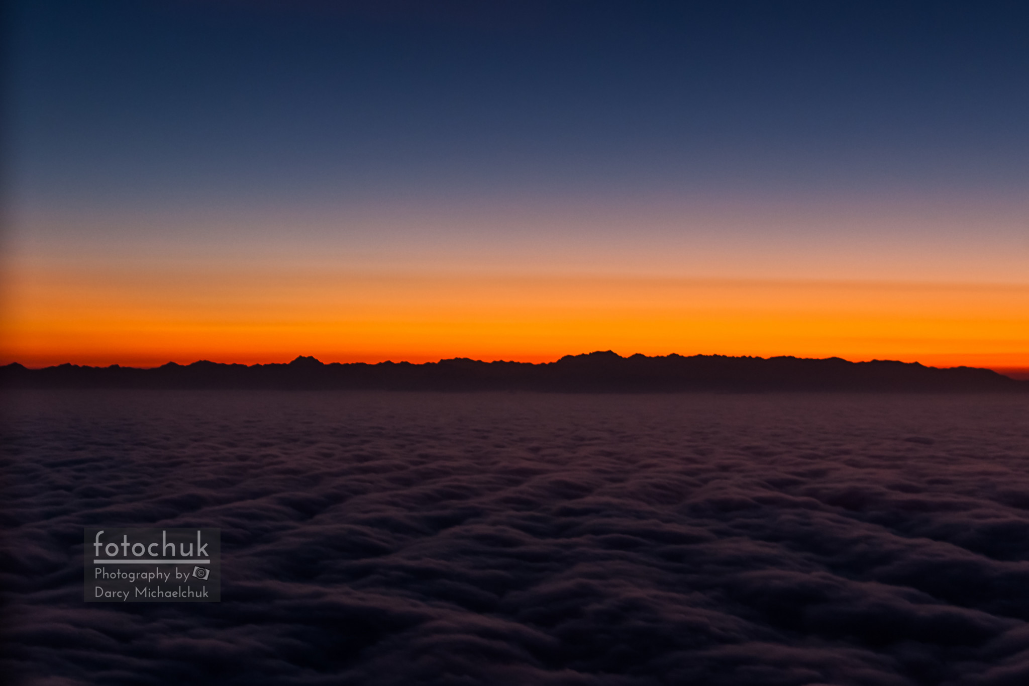 Mountain Silhouette Over Sea of Clouds