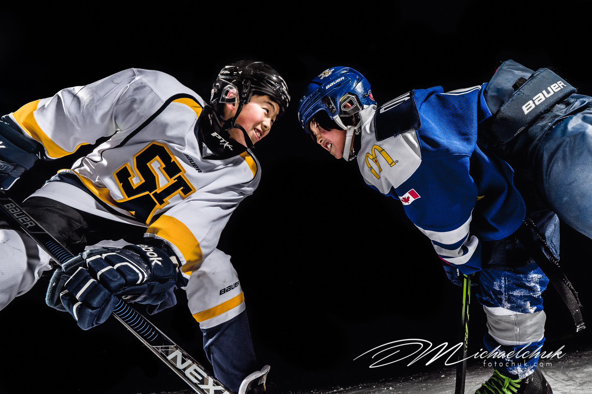 Brothers fighting for the puck on the outdoor ice at night.